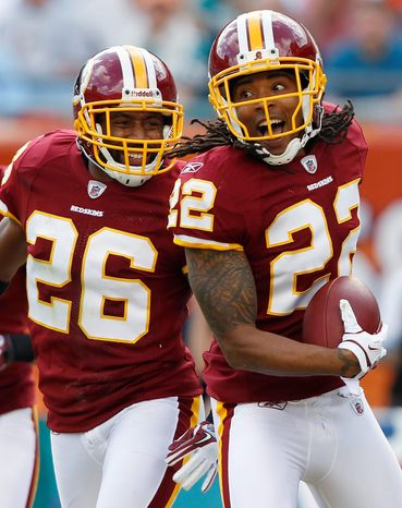 Washington Redskins defensive back Kevin Barnes (22) celebrates after his interception during the first quarter of an NFL football game against the Miami Dolphins, Sunday, Nov. 13, 2011, in Miami. At left is cornerback Josh Wilson (26). (AP Photo/Hans Deryk)
