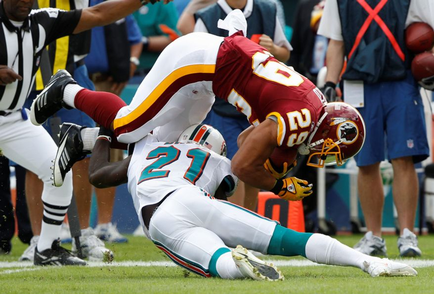Washington Redskins running back Roy Helu (29) is stopped by Miami Dolphins cornerback Vontae Davis (21) in the first quarter. (AP Photo/Hans Deryk)