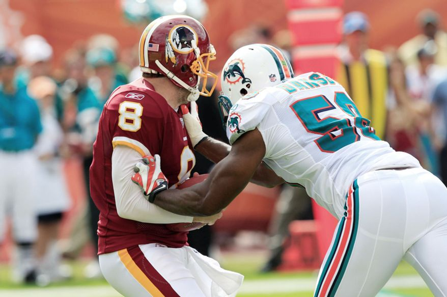 Washington Redskins quarterback Rex Grossman (8) is sacked by Miami Dolphins inside linebacker Karlos Dansby (58) during the first quarter. (AP Photo/Wilfredo Lee)