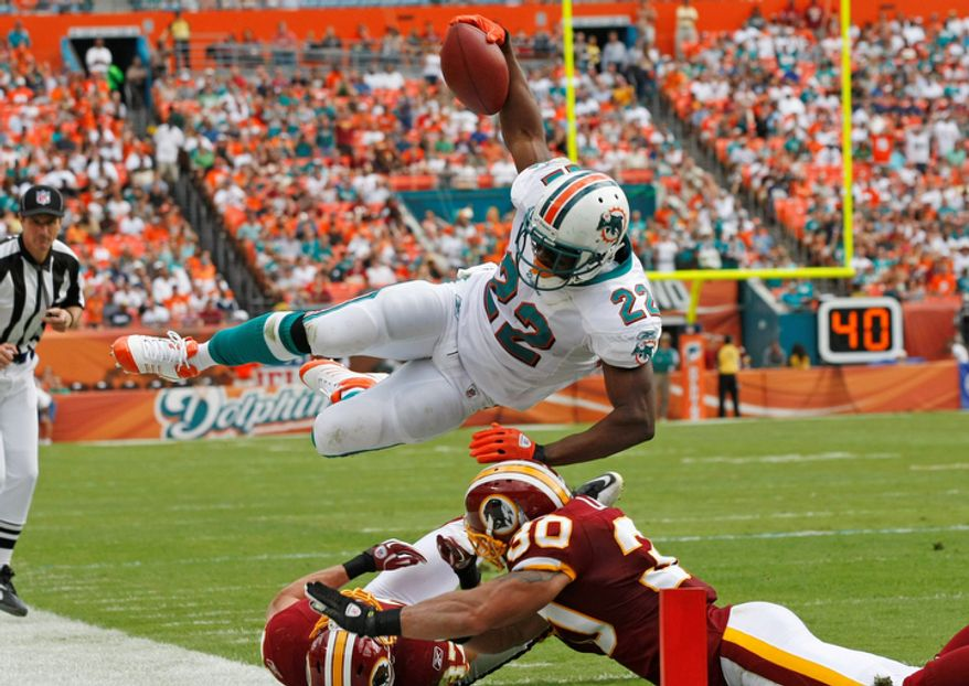 Miami Dolphins running back Reggie Bush (22) leaps just short of the end zone as Washington Redskins strong safety LaRon Landry (30) and another Washington player defend during the first half. (AP Photo/Hans Deryk)