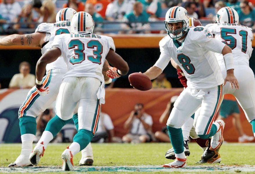 Miami Dolphins quarterback Matt Moore (8) hands off the football to running back Daniel Thomas (33) during the third quarter. (AP Photo/Hans Deryk)