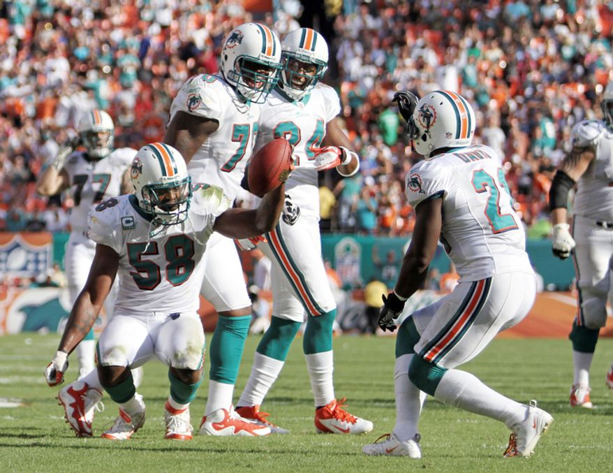 Miami Dolphins inside linebacker Karlos Dansby (58) celebrates with defensive end Kendall Langford (70), cornerback Sean Smith (24) and cornerback Vontae Davis (21) after getting an interception during the fourth quarter. (AP Photo/J Pat Carter)