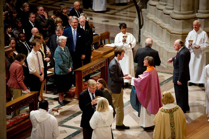 A visitor receives communion from The Reverend Dr. Mariann Edgar Buddle, right, after she is seated as the ninth bishop of Washington at the service of Holy Eucharist. (Andrew Harnik / The Washington Times)