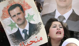 Pro-Syrian regime protesters shout slogans and hold portraits of Syrian President Bashar Assad during a demonstration in Damascus, Syria, on Nov. 13, 2011, against the Arab League decision to suspend Syria. (Associated Press)