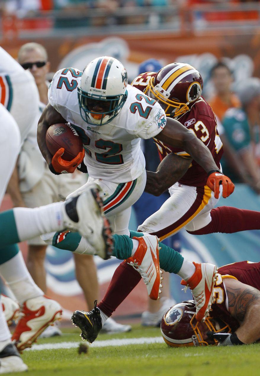 Miami Dolphins running back Reggie Bush gets past Washington Redskins cornerback DeAngelo Hallon his way to scoring a touchdown during the fourth quarter Sunday, Nov. 13, 2011, in Miami. (AP Photo/Hans Deryk)