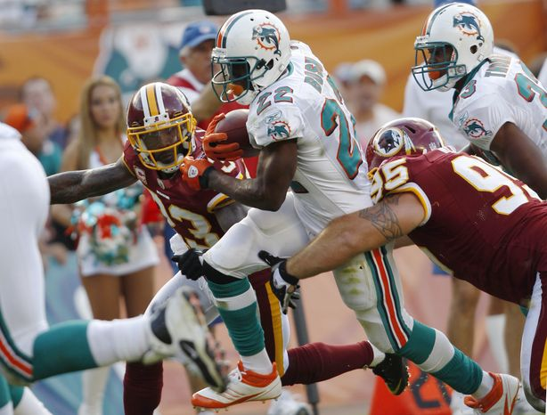 Miami Dolphins running back Reggie Bush runs for a touchdown as Washington Redskins cornerback DeAngelo Hall and Washington Redskins nose tackle Chris Neild defend during the fourth quarter Sunday, Nov. 13, 2011, in Miami. The Dolphins defeated the Redskins 20-9. (AP Photo/Hans Deryk)
