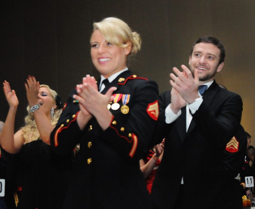 Cpl. Kelsey De Santis and her date, Justin Timberlake, applaud the guest speaker at Friday night's Marine Corps Ball in Richmond, Va. (Marine Corps Base Quantico Public Affairs via Associated Press)