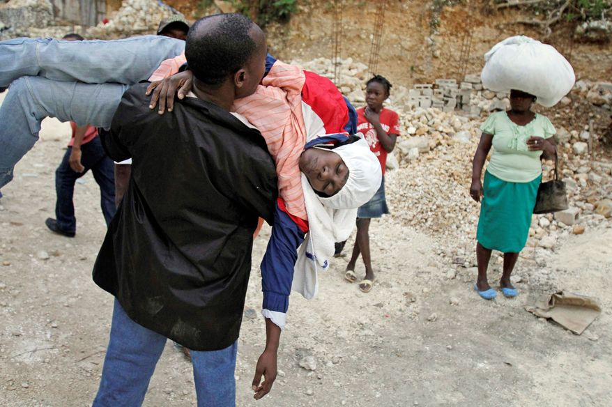 At top, a woman suffering cholera symptoms is carried to a Port-au-Prince hospital in March. Haiti's Health Ministry says a deadly epidemic that began in October 2010 has sickened nearly 500,000 and killed more than 6,500. (Associated Press)