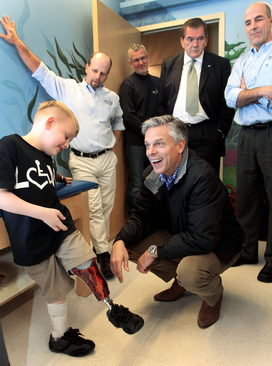 Carter Mead shows off designs on his prosthetic leg as GOP presidential candidate Jon Huntsman tours a prosthetics firm Friday in Manchester, N.H. (Associated Press)