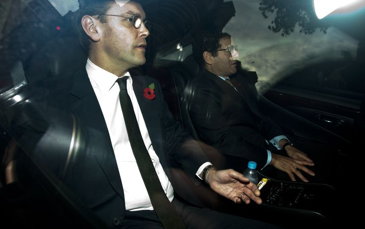 News Corp. executive James Murdoch (left) is driven away from a drive-in entrance at Portcullis House after his second appearance before British parliamentarians investigating the country's phone hacking scandal in London, on Nov. 10, 2011. (Associated Press)