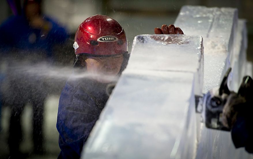 """Artisan ice sculptors from Harbin, China work on heavy blocks of crystal clear ice as they work on the huge ice slide, and as others on their team work to create colorful scenes from the DreamWorks' production of """"Merry Madagascar"""" for this years ICE! show in Oxon Hill, Md, Thursday, November 9, 2011.  (Rod Lamkey Jr. / The Washington Times)"""