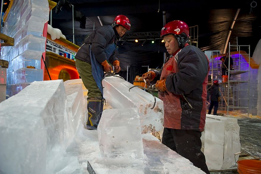 "Artisan ice sculptors from Harbin, China use ice picks to move large blocks of ice into place as they work to create colorful scenes from the DreamWorks' production of ""Merry Madagascar"" for this years ICE! show in Oxon Hill, Md, Thursday, November 9, 2011. 40 men from Harbin, China return here to create a frozen wonderland, complete with an ice slide and characters from the movie. These men are a part of the team which creates the famous Harbin Ice Festival in Harbin, China every year. Some of the sculptures are comprised of colored ice blocks, yielding brilliant tones and deep hues for highlights and accents. Others are illuminated internally by some of the exhibit's 1,400 specially designed LED tube lights, evoking the ice lanterns of old. Others are engineered to support the presence of thousands of visitors over the exhibit's lifespan. (Rod Lamkey Jr. / The Washington Times)"