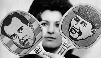 A 1971 photo of a woman holding pingpong paddles bearing caricatures of President Nixon and China's Mao Zedong recalls that year's Chinese-U.S. match in Dortmund, Germany, which led to Nixon's historic visit to Beijing. (Associated Press)