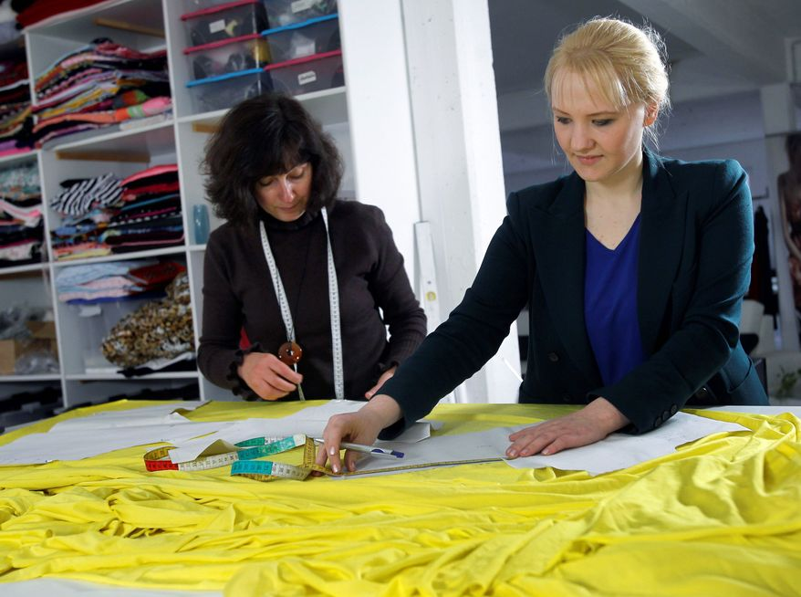 """German fashion designer Anke Domaske (right) - with seamstress Tatjana Berthold at their studio in Hanover, Germany - is the designer of an award-winning new textile made entirely from milk that is environmentally friendly and soothing for people with skin allergies. Called """"Qmilch,"""" the fabric drapes and folds like silk but can be washed and dried like cotton.  (Associated Press)"""