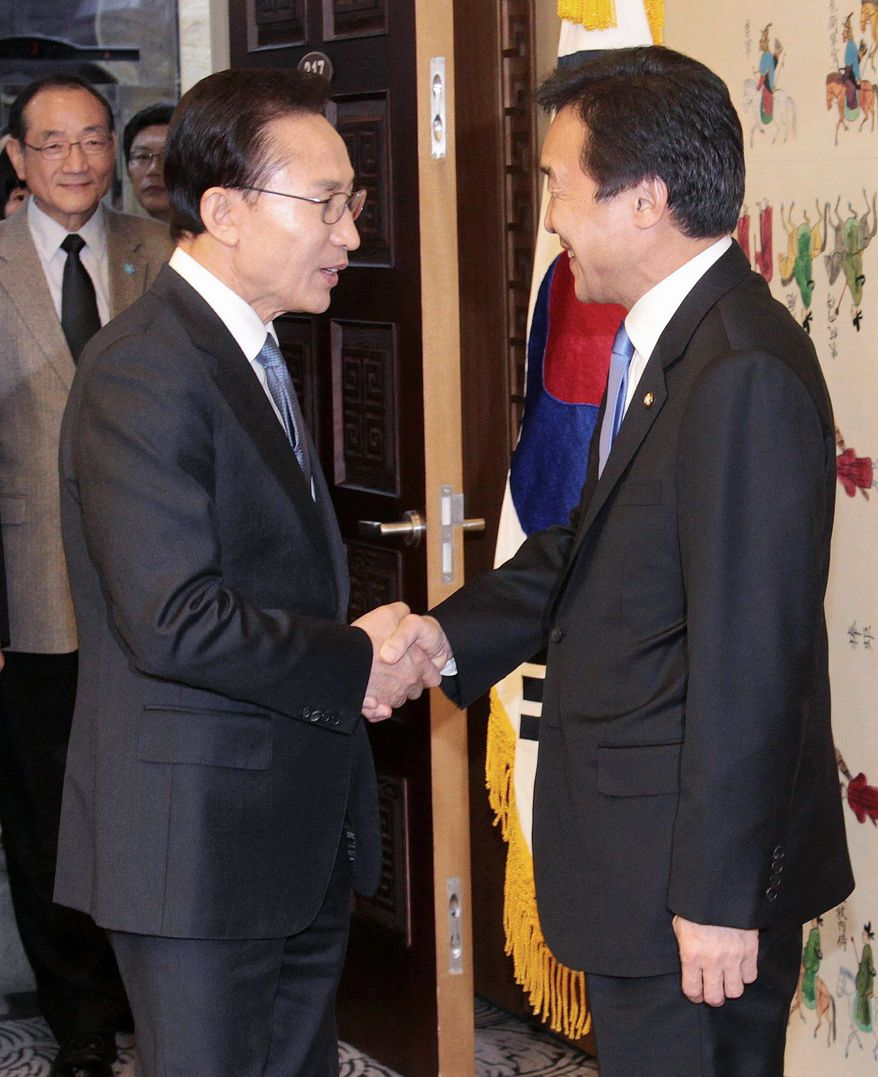 South Korean President Lee Myung-bak (left) shakes hands with Sohn Hak-kyu, chairman of the leading opposition Democratic Party, before their meeting at the National Assembly in Seoul on Tuesday. Mr. Lee made a rare visit to the National Assembly to try to break a deadlock on passage of a long-stalled free-trade agreement with the United States. (Associated Press)