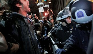 An Occupy Wall Street protester yells out at police after being ordered to leave Zuccotti Park during an overnight sweep. At about 1 a.m. Tuesday, police handed out notices from the park's owner, Brookfield Office Properties, and the city saying that the park had to be cleared because it had become unsanitary and hazardous. (Associated Press)