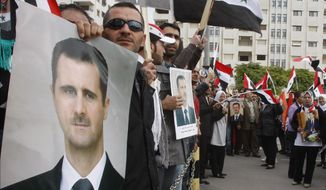 Pro-Syrian regime protesters hold portraits of Syrian President Bashar Assad and shout slogans against the Arab League as they gather in Damascus, Syria, on Nov. 14, 2011, outside the Syrian foreign ministry. (Associated Press)