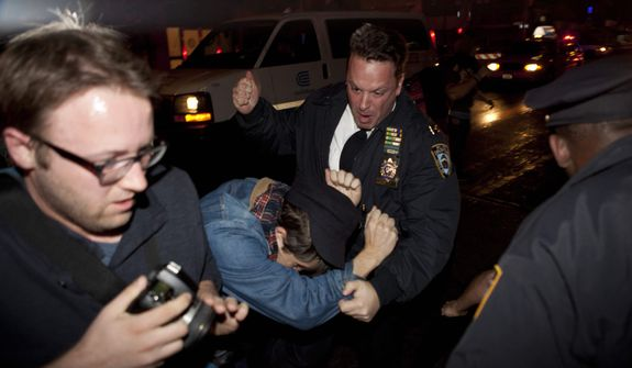 An Occupy Wall Street protestor draws contact from a police officer near Zuccotti Park after being ordered to leave the longtime encampment in New York, Tuesday, Nov. 15, 2011, in New York, after police ordered demonstrators to leave their encampment in Zuccotti Park. (AP Photo/John Minchillo)