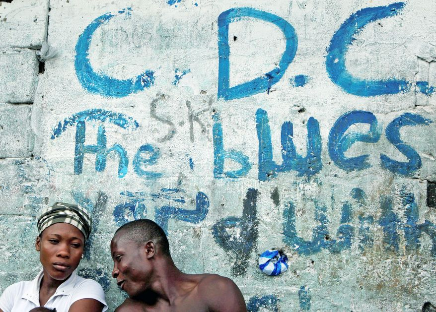 """Young people (left) sit against the wall of a home marked with graffiti reading """"C.D.C.,"""" the acronym for the opposition political party. (Associated Press)"""