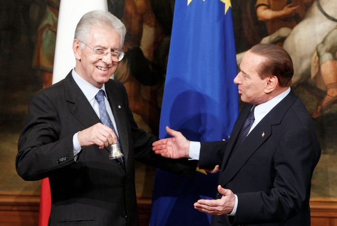Italian Prime Minister Mario Monti (left) receives a small bell from former Prime Minister Silvio Berlusconi after the swearing-in ceremony at the prime minister's office at Chigi Palace in Rome on Wednesday. The bell is used by the prime minister to call attention during Cabinet meetings. (Associated Press)