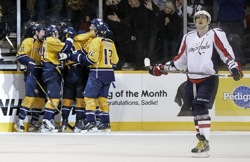 Washington Capitals left wing Alex Ovechkin, right, of Russia, looks up at the scoreboard as Nashville Predators players celebrate a goal by Martin Erat in the third period of an NHL hockey game Tuesday, Nov. 15, 2011, in Nashville, Tenn. The Predators won 3-1. (AP Photo/Mark Humphrey)