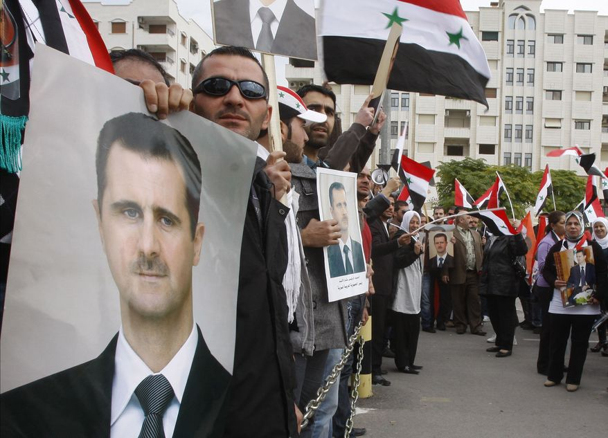 Pro-Syrian regime protesters hold portraits of Syrian President Bashar Assad and shout slogans against the Arab League outside the Syrian foreign ministry in Damascus, Syria, on Nov. 14, 2011. (Associated Press)