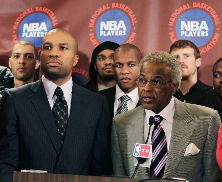Surrounded by NBA basketball players, Executive Director of the National Basketball Players Association Billy Hunter, right, speaks to the media while Players Association president Derek Fisher listens during a news conference after a meeting of the players' union in New York, Monday, Nov. 14, 2011. The NBA players rejected the league's latest offer and disbanded from the union. (AP Photo/Seth Wenig)