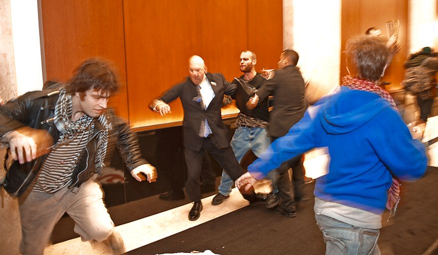 Demonstrators with Occupy D.C. are forcibly removed from the lobby of the Victor Building during a march in downtown Washington, D.C., Tuesday, Nov. 15, 2011, to show support for the Occupy Wall Street movement. (Rod Lamkey Jr./The Washington Times)