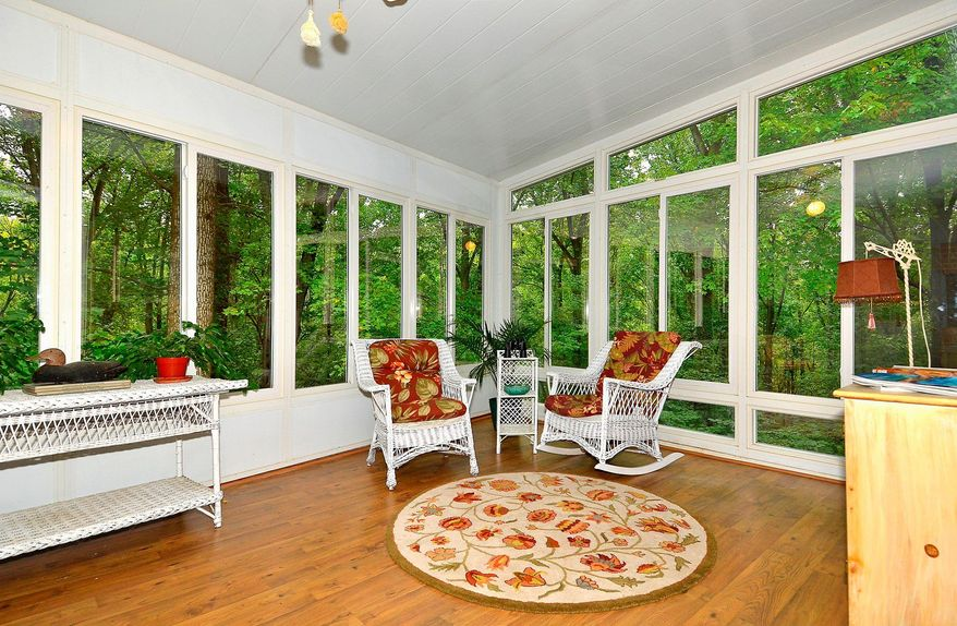 An open patio was enclosed into a sunroom with windows on three sides and views of the woods behind the home.