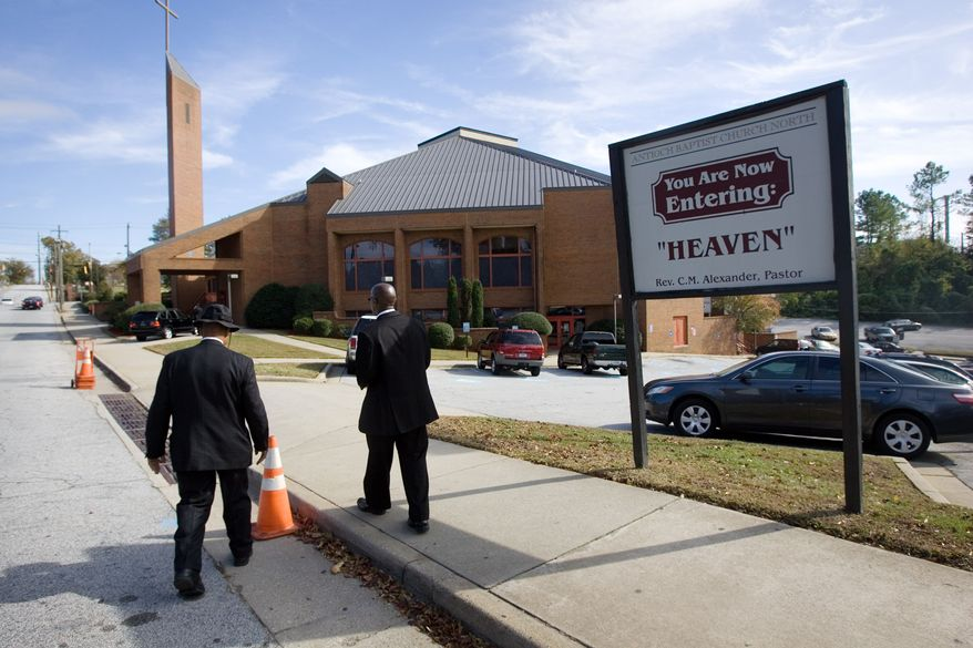 A Security detail walks back to the property of Antioch Baptist Church North, which is the church Republican Presidential hopeful Herman Cain attends, after services on Sunday Nov. 6, 2011. (AP Photo/John Amis)
