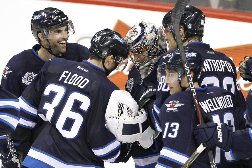 Winnipeg Jets teammates congratulate goalie Ondrej Pavelec after the Jets defeated the Tampa Bay Lightning 5-2 Monday, Nov. 14, 2011, in Winnipeg, Manitoba. (AP Photo/The Canadian Press, John Woods)