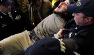 An Occupy Wall Street protester yells as he is arrested by the police after blocking an intersection near the New York Stock Exchange on Nov. 17, 2011. (Associated Press)