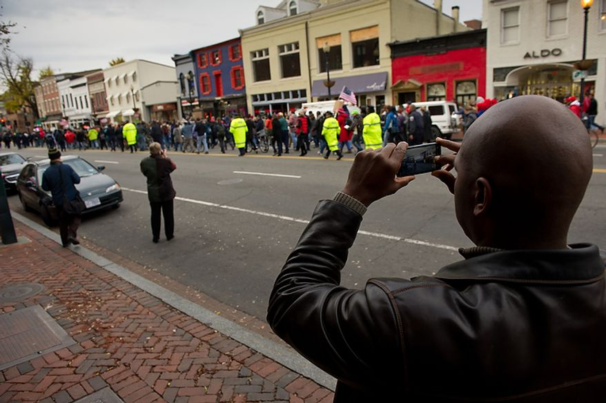 A man takes a photo of the Occupy DC protesters as they march through Georgetown to the Key Bridge which connects Georgetown to Northern Virginia, Washington, DC, Thursday, November 17, 2011. (Andrew Harnik/The Washington Times)