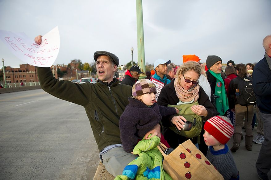 Ben Riddleberger of Baltimore, Md, is joined his his wife Abbie and sons Simon, 2, (left) and Peter, 5, as they join combination of different protest groups converging on the Key Bridge in Washington, DC, Thursday, November 17, 2011. (Rod Lamkey Jr. / The Washington Times)