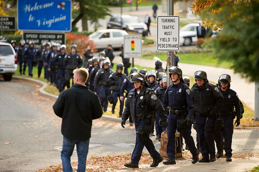 Arlington County Police officers wearing riot helmets take position on the Virginia side of Key Bridge as Occupy DC protesters make their way from Georgetown to Northern Virginia after marching down K Street from McPherson Square, Arlington, VA, Thursday, November 17, 2011. (Andrew Harnik/The Washington Times)