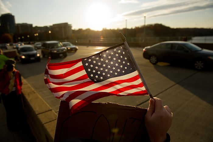 An Occupy DC protester waves an American flag at drivers on Key Bridge after the protesters marchd from McPherson Square down K Street to the Key Bridge which connects Georgetown to Northern Virginia, Washington, DC, Thursday, November 17, 2011. (Andrew Harnik/The Washington Times)