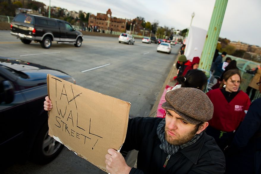 Adam Chadwich of Brooklyn, NY holds a sign out for drivers on Key Bridge after the protesters marched from McPherson Square down K Street to the Key Bridge which connects Georgetown to Northern Virginia, Washington, DC, Thursday, November 17, 2011. (Andrew Harnik/The Washington Times)