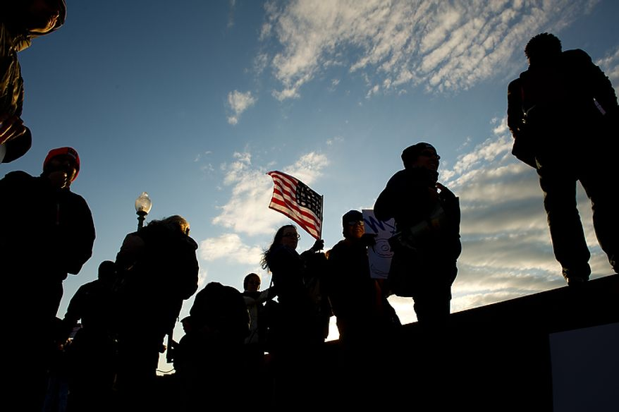 Occupy DC protesters chant and wave American flags at drivers on Key Bridge after the protesters marched from McPherson Square down K Street to the Key Bridge which connects Georgetown to Northern Virginia, Washington, DC, Thursday, November 17, 2011. (Andrew Harnik/The Washington Times)