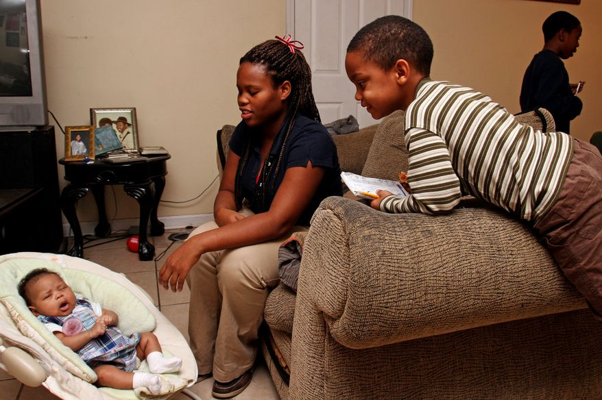 **FILE** Javonte Robinson (right), 4, looks in on his 2-month-old cousin, Bre'Azia Aaliyah Bryant, as she rests with her mother, Gautier High School student Jasmine Jones, 18, at her house in Gautier, Miss. (Associated Press/The Sun Herald)