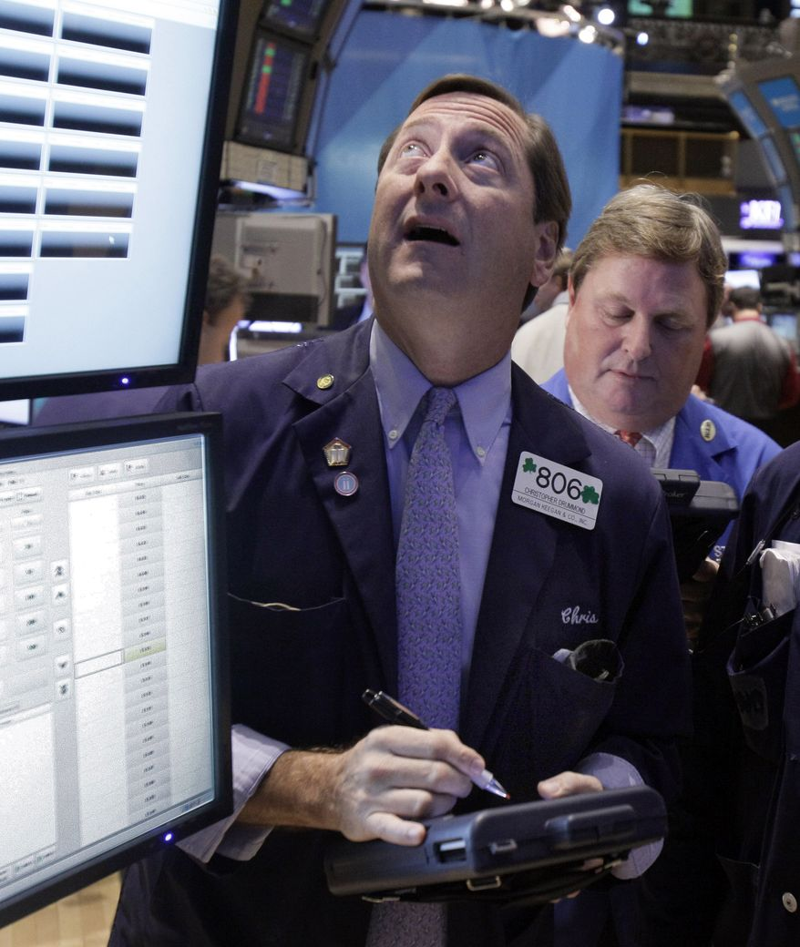 Trader Christopher Drummond (left) works on the floor of the New York Stock Exchange on Nov. 17, 2011. (Associated Press)