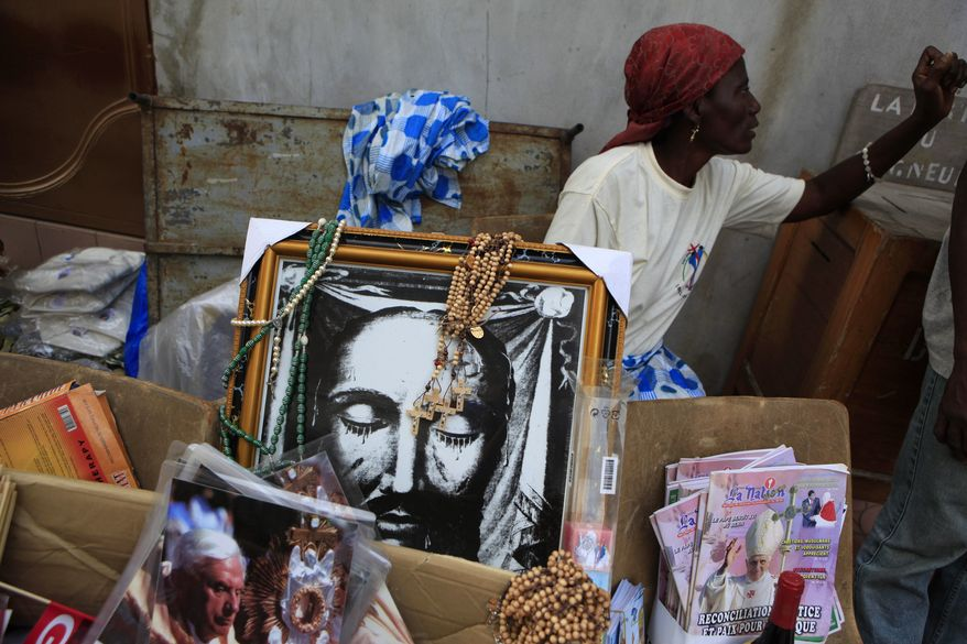 A woman selling memorabilia ahead of Pope Benedict XVI's visit waits for clients outside St. Michael Church in Cotonou, Benin, Friday, Nov. 18, 2011. (AP Photo/Rebecca Blackwell)