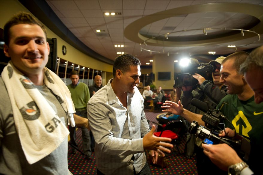 Washington Nationals' catcher (3) Wilson Ramos (center) is welcomed by team mates Ryan Zimmerman (11) (left) and Stephen Lombardozzi (1) (right) after offering remarks to reporters about his recent abduction in front of his family home in Venezuela, in the team's clubhouse in Washington, DC, Friday, November 18, 2011. (Rod Lamkey Jr. / The Washington Times)