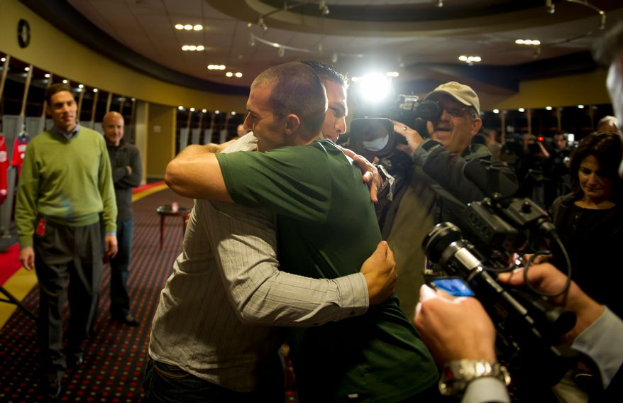 Washington Nationals' catcher (3) Wilson Ramos (left) is hugged by team mate Stephen Lombardozzi (1) (right) after offering remarks to reporters about his recent abduction in front of his family home in Venezuela, in the team's clubhouse in Washington, DC, Friday, November 18, 2011. (Rod Lamkey Jr. / The Washington Times)