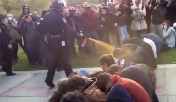 In this image made from video, a police officer uses pepper spray as he walks down a line of Occupy demonstrators sitting on the ground at the University of California, Davis on Friday, Nov. 18, 2011. The video - posted on YouTube - was shot Friday as police moved in on more than a dozen tents erected on campus and arrested 10 people, nine of them students. (AP Photo/Thomas K. Fowler)