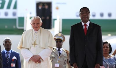 Pope Benedict XVI stands with Benin's President Yayi Boni during an airport welcome ceremony in Cotonou, Benin Friday, Nov. 18, 2011. (AP Photo/Rebecca Blackwell)