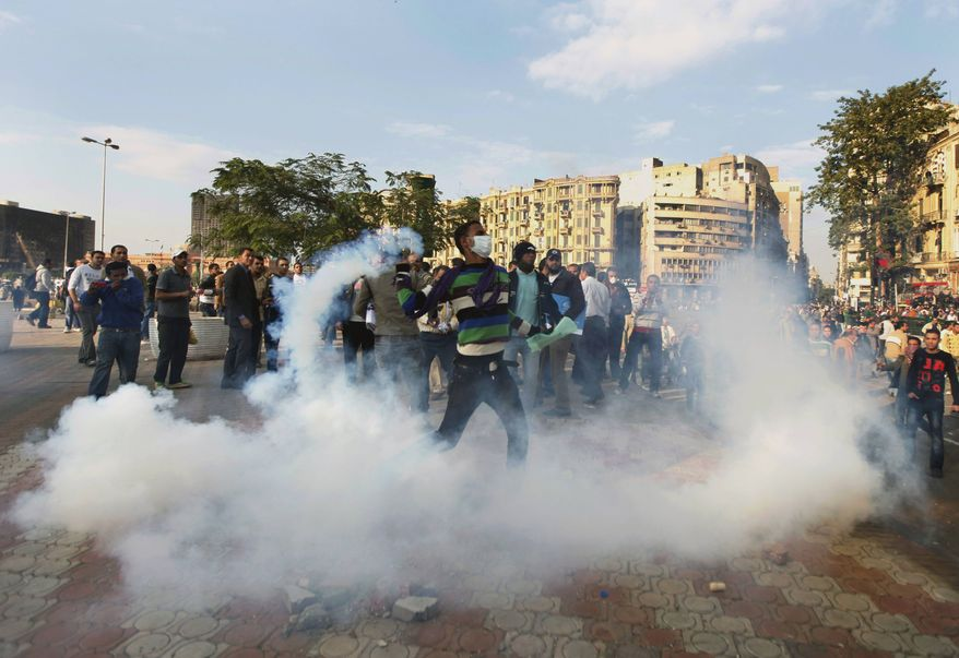 A protester throws a tear gas grenade back at Egyptian riot police in Tahrir Square in Cairo, Egypt, Saturday, Nov. 19, 2011. (AP Photo/Khalil Hamra)