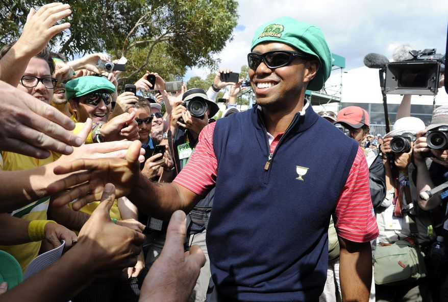 Tiger Woods of the U.S. team dons a cap after receiving it from Australian fans at the Presidents Cup. The Americans won 19-15 to improve to 7-1-1 in the series. (Associated Press)
