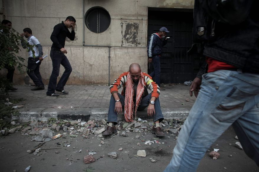 A protester overcome by tear gas rests from clashes with Egyptian police Sunday near the interior ministry in Cairo. (Associated Press)