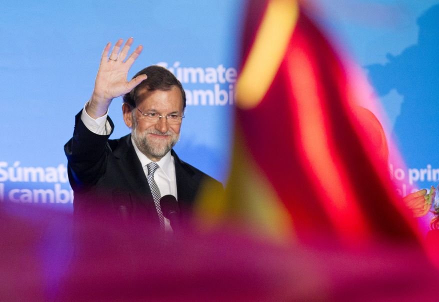 Popular Party candidate Mariano Rajoy waves to gleeful supporters in Madrid on Sunday. With his party winning a huge majority in the Spanish parliament, Mr. Rajoy is set to become the nation's next prime minister. (Associated Press)