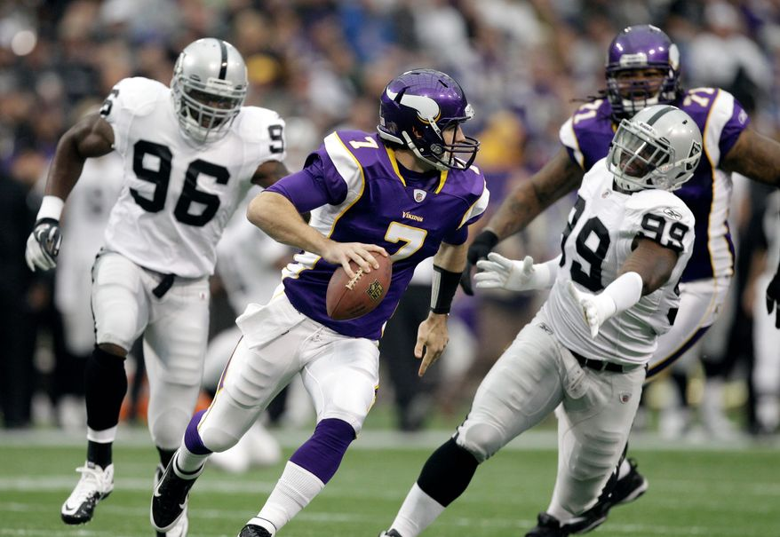 Minnesota Vikings quarterback Christian Ponder (7) runs from Oakland Raiders defensive end Lamarr Houston (99) and linebacker Kamerion Wimbley (96) during the first half Sunday, Nov. 20, 2011, in Minneapolis. (AP Photo/Charlie Neibergall)